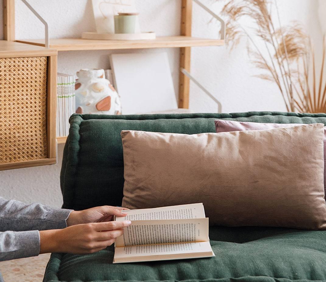 Lectura en el sofá de un salón acogedor decorado con cojines beige y malva